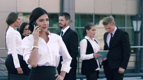 Het donkerbruine bedrijfsvrouw spreken op de telefoon voor de camera en op de achtergrond haar collega's bevindt zich stock video