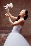 Het donkerbruine bruid stellen in studio met bloemen Stock Afbeeldingen