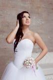 Het donkerbruine bruid stellen in studio met bloemen Royalty-vrije Stock Fotografie