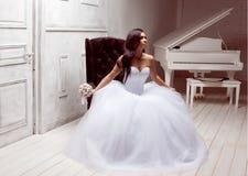 Het donkerbruine bruid stellen in studio met bloemen Royalty-vrije Stock Foto's