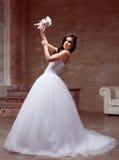 Het donkerbruine bruid stellen in studio met bloemen Royalty-vrije Stock Afbeeldingen