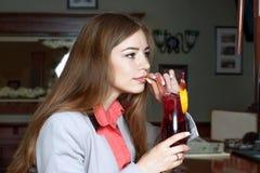 Het donkerbruine drinken van een zitting van het buissap op de bar stock foto