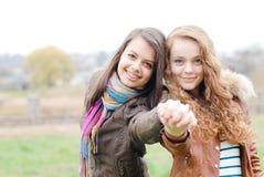 Het donkerbruine en blonde haired meisjesvrienden lachen Stock Afbeelding