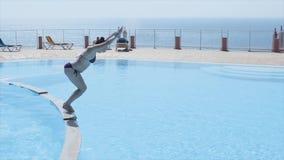 Het donkerbruine jonge meisje duikt in open zwembad De zonnige dag van de zomer vakantie Plons Blauw water stock video