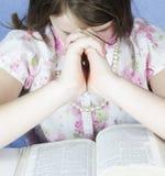 Het donkerbruine Meisje bidt met Bijbel Stock Afbeelding