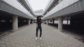 Het donkerbruine meisje danst en voert moderne hiphopdans in parkeren, vrij slag in industrieel uit stock footage