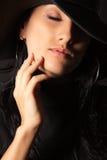 Het donkerbruine meisje in de hoed raakt zacht uw gezicht Stock Foto