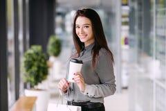 Het donkerbruine meisje drinkt een koffie van een grote document kop Stock Foto's
