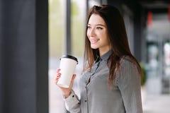 Het donkerbruine meisje drinkt een koffie van een grote document kop Royalty-vrije Stock Foto