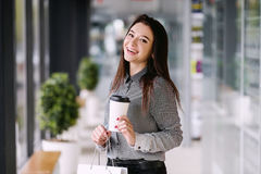 Het donkerbruine meisje drinkt een koffie van een grote document kop Royalty-vrije Stock Foto's