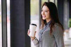 Het donkerbruine meisje drinkt een koffie van een grote document kop Stock Foto
