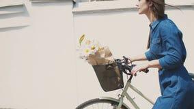 Het donkerbruine meisje in een kleding werpt terug haar haar en loopt haar fiets met bloemen in een mand, 4k, steadicam schot stock video