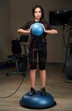 Het donkerbruine meisje in EMS-kostuum bevindt zich op bosubal en houdt blauwe bal stock fotografie