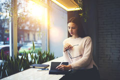 Het donkerbruine meisje in glazen voert dagelijks werkcliënten uit die van beste ideeën en oplossing nota nemen in persoonlijk no Stock Afbeeldingen