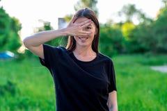 Het donkerbruine meisje glimlacht gelukkig De zomer in openlucht in verse lucht Het gebaar van de hand en toont aan dat zij piepe Royalty-vrije Stock Afbeelding