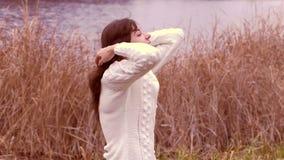 Het donkerbruine meisje maakt haar haar in een sweater recht stock video