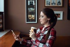 Het donkerbruine meisje met glazen en een overhemd, in de middag bij een koffie door het venster, drinken thee in de ochtend Hij Royalty-vrije Stock Fotografie