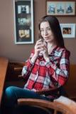 Het donkerbruine meisje met glazen en een overhemd, in de middag bij een koffie door het venster, drinken thee in de ochtend hold Stock Afbeelding