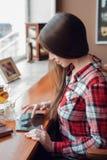 Het donkerbruine meisje met lang mooi haar in haar overhemd, in de middag bij een koffie door het venster, bekijkt mobiel Royalty-vrije Stock Foto