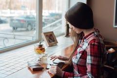 Het donkerbruine meisje met lang mooi haar in haar overhemd, in de middag bij een koffie door het venster, bekijkt mobiel Stock Afbeelding
