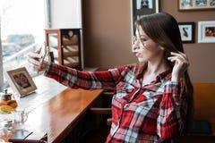 Het donkerbruine meisje met lang mooi haar in haar overhemd, in de middag bij een koffie door het venster, neemt beelden op a Royalty-vrije Stock Fotografie