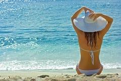 Het donkerbruine meisje ontspannen op het overzeese strand Stock Foto