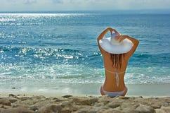 Het donkerbruine meisje ontspannen in water op het strand Stock Foto's