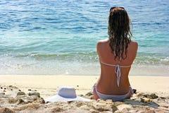 Het donkerbruine meisje ontspannen in water op het strand Stock Afbeeldingen