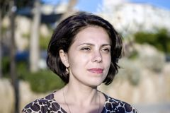 Het donkerbruine meisje op de kust van de Middellandse Zee, onderzoekt de afstand Stock Foto