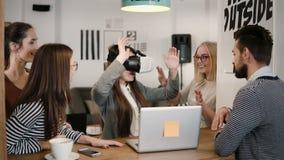 Het donkerbruine meisje probeert app voor VR-glazen van de helm de virtuele werkelijkheid haar vrienden en collega's ondersteunen Stock Afbeeldingen