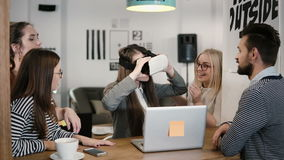 Het donkerbruine meisje probeert app voor VR-glazen van de helm de virtuele werkelijkheid haar vrienden en collega's ondersteunen Royalty-vrije Stock Afbeelding