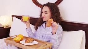 Het donkerbruine meisje stellen met gebakje en sap in bed stock footage