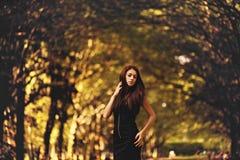 Het donkerbruine meisje stelt elegant in het de herfstpark Royalty-vrije Stock Foto's
