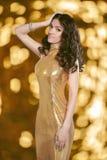 Het donkerbruine meisje van de schoonheidsglamour in geïsoleerde Manier gouden kleding Stock Afbeelding