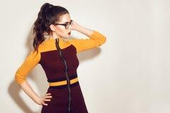 Het donkerbruine modelmeisje die van de schoonheidsmanier modieuze glazen dragen Sexy vrouw met perfecte make-up, in oranje en ro stock foto