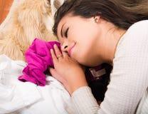 Het donkerbruine vrouw liggen op stapel van kleren die en schijnt te slapen, garderobe het winkelen manierconcept glimlachen Stock Fotografie