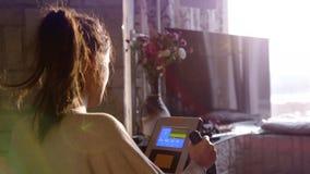 Het donkerbruine vrouw praktizeren op de fietssimulator door venster die op de stad tijdens zonsondergang met de gevolgen van de  Stock Foto