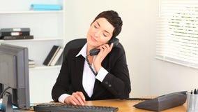 Het donkerbruine vrouw typen op laptop en het beantwoorden van de telefoon stock videobeelden