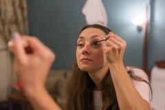 Het donkerbruine vrouw van toepassing zijn maakt omhoog & x28; schilder haar eyelashes& x29; voor een avonddatum voor een spiegel stock foto's