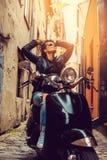 Het donkerbruine vrouwelijke stellen op scooter Royalty-vrije Stock Foto