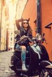 Het donkerbruine vrouwelijke stellen op scooter Royalty-vrije Stock Foto's