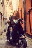 Het donkerbruine vrouwelijke stellen op scooter Stock Afbeelding