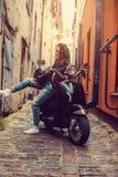 Het donkerbruine vrouwelijke stellen op scooter Stock Afbeeldingen