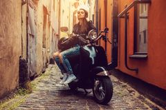 Het donkerbruine vrouwelijke stellen op scooter Stock Fotografie