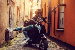 Het donkerbruine vrouwelijke stellen op scooter Royalty-vrije Stock Afbeelding