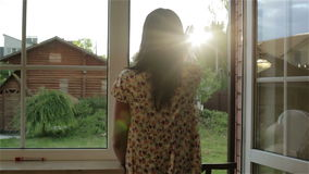 Het donkerbruine vrouwenkielzog omhoog en geniet van zonsopgang bij het open venster stock videobeelden