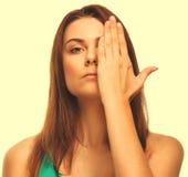 Het donkerbruine vrouwenmeisje behandelde haar gezichts halve die hand op wit wordt geïsoleerd stock afbeelding