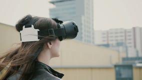 Het donkerbruine vrouwenmeisje met golvend haar gebruikt 3D Virtuele Werkelijkheidshoofdtelefoon op het dak 4K Royalty-vrije Stock Afbeeldingen