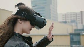 Het donkerbruine vrouwenmeisje met golvend haar gebruikt 3D Virtuele Werkelijkheidshoofdtelefoon op het dak 4K Royalty-vrije Stock Fotografie