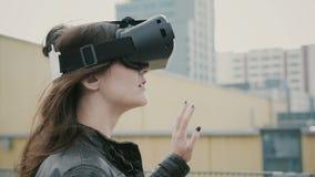 Het donkerbruine vrouwenmeisje met golvend haar gebruikt 3D Virtuele Werkelijkheidshoofdtelefoon op het dak 4K Stock Foto